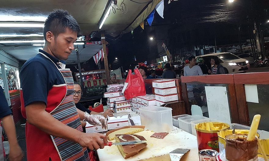 A worker at Martabak 65a in Jakarta applying butter on top of a freshly cooked sweet murtabak. Rich chocolate min jiang kueh-style pancake from Martabak Markobar in Indonesia.