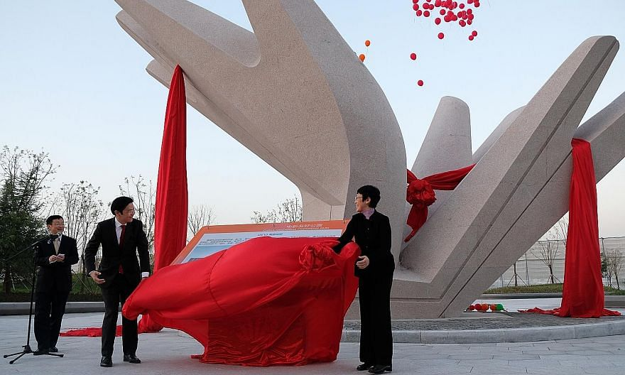 National Development Minister Lawrence Wong and China's Vice-Minister of the Ministry of Housing and Urban-Rural Development, Ms Huang Yan, unveiling a sculpture outside the China-Singapore Friendship Library to commemorate the Tianjin Eco-city's 10t