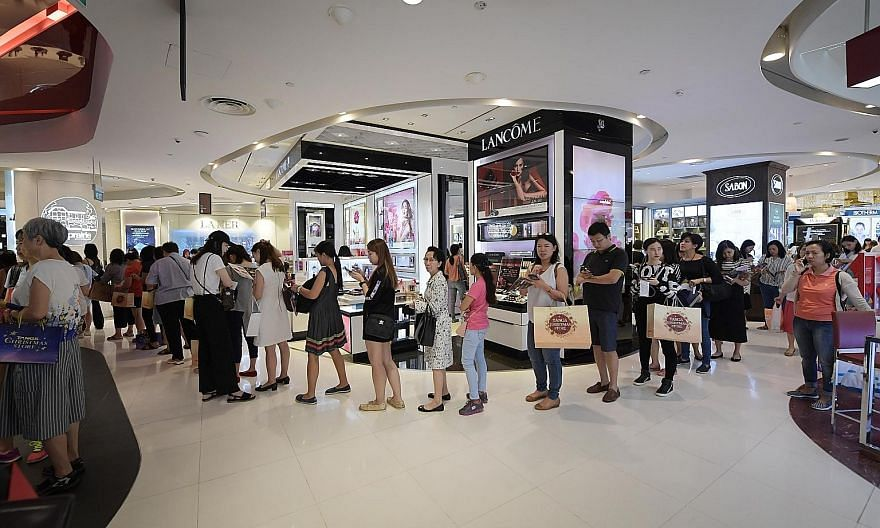 Above: A queue for beauty vouchers at Tangs in Orchard Road on Black Friday. Tangs was among the stores that saw throngs of shoppers eager to snap up deals and limited-edition items. Below: At department store Metro's Paragon outlet, shoppers could g