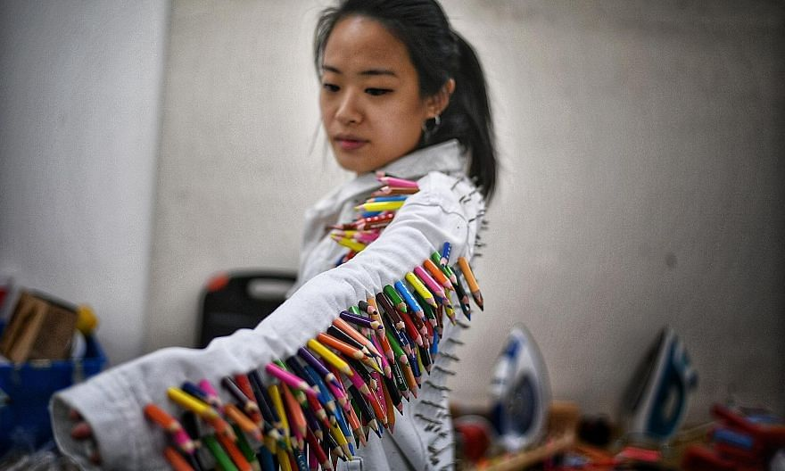 Charmaine Poh of Proxy models a coat studded with colour pencils and nails designed by the collective for Home(work), an installation about domestic labour and creativity.