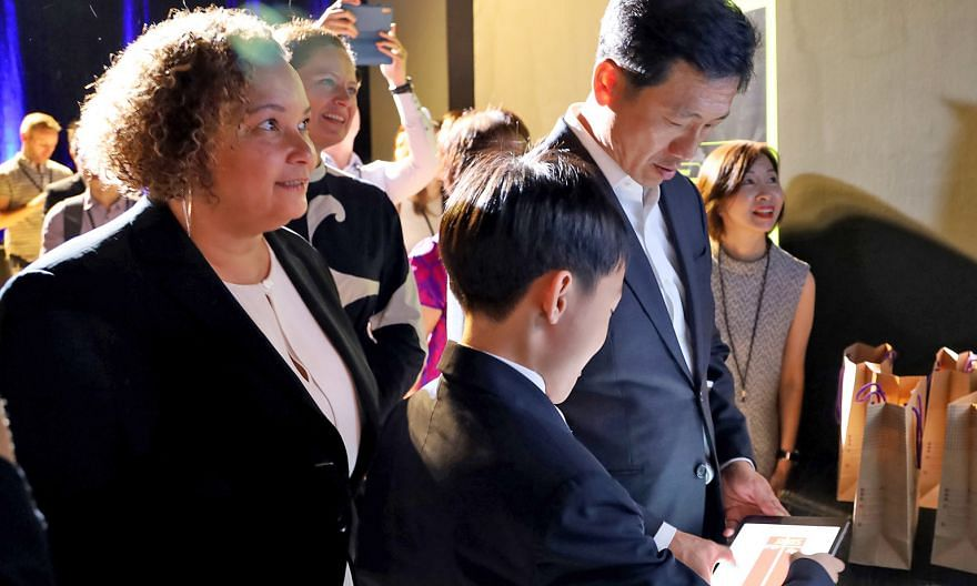 Education Minister Ong Ye Kung trying out a game with Pathlight School student Kaeden Chan at yesterday's launch of coding programme Swift Accelerator. With them was Ms Lisa Jackson from Apple.