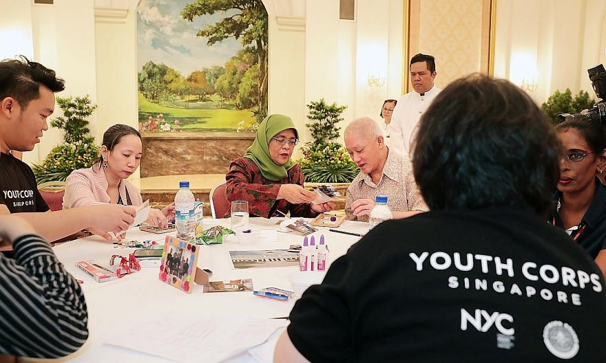 President Halimah Yacob participating in an art activity with patients from the Institute of Mental Health (IMH) where they decorated photo frames together at the Istana. The activity followed a garden tour where 39 guests from IMH explored the lawn