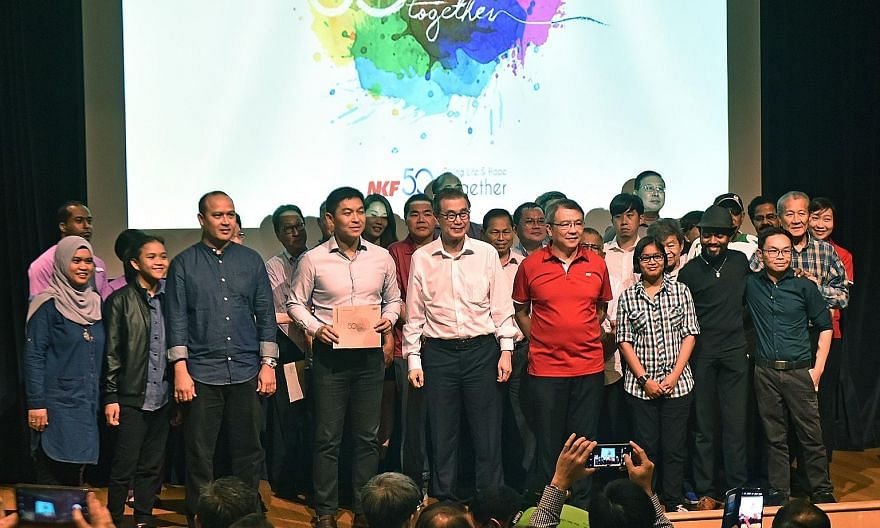 Speaker of Parliament Tan Chuan-Jin (holding a copy of the new commemorative book), NKF chairman Koh Poh Tiong (centre) and NKF chief executive Tim Oei (in red) on stage with participants in yesterday's event marking the foundation's 50th anniversary