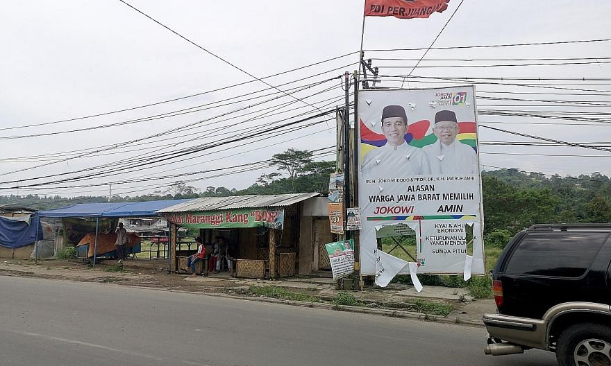 Indonesians at an election campaign rally in support of Mr Prabowo and his running mate Sandiaga Uno in Bogor in the deeply religious West Java province late last month. A vandalised campaign poster of incumbent President Joko Widodo and his running