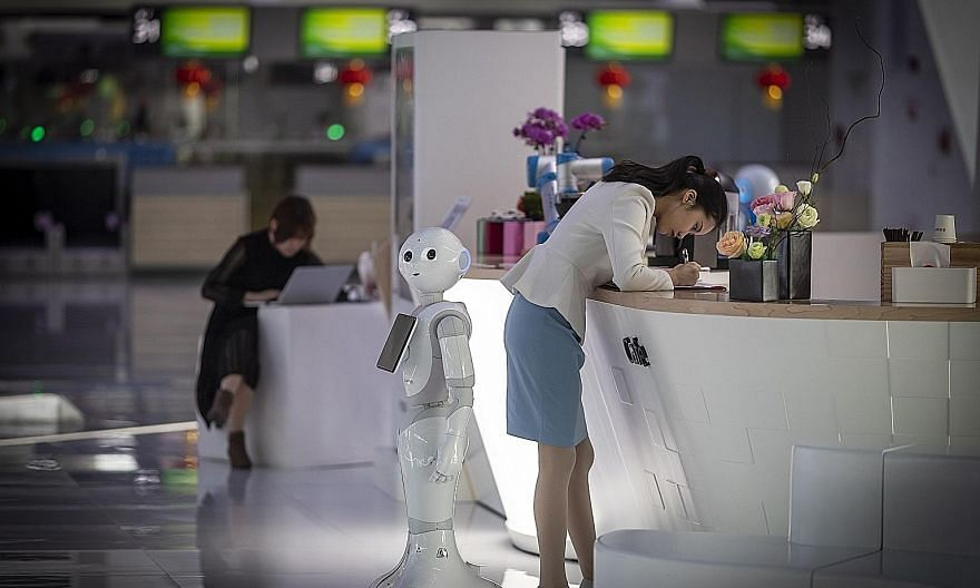 """An AI robot operates at the Baiyun International Airport in Guangzhou, China. Because automation will replace and change many tasks done by humans today, the concept of a """"job"""" is changing fundamentally."""