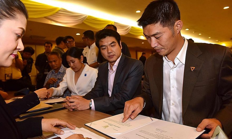 Future Forward Party leader Thanathorn Juangroongruangkit (right) and secretary-general Piyabutr Saengkanokkul (beside him) receiving the official certification as elected MPs in Bangkok earlier this month. PHOTO: AGENCE FRANCE-PRESSE