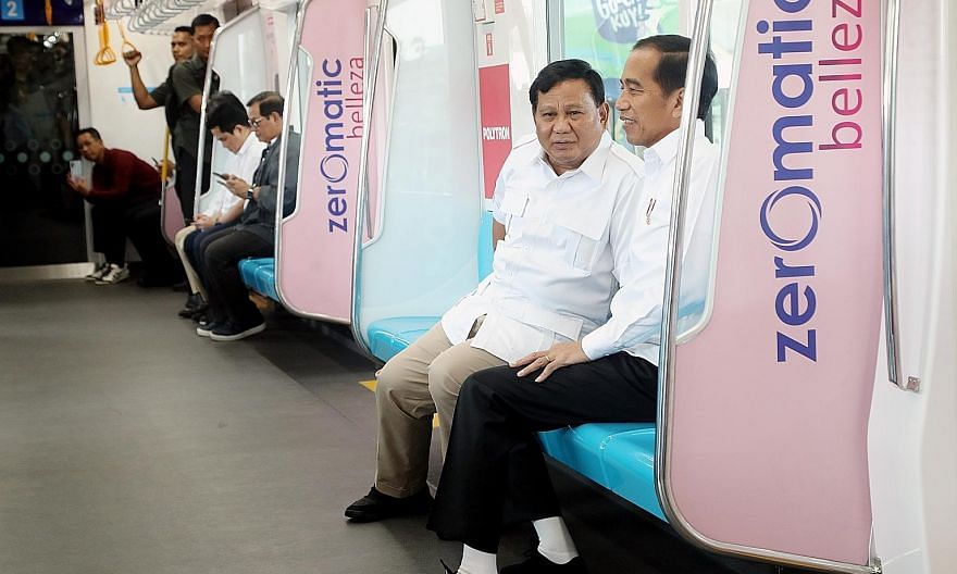 President Joko Widodo (right) with retired army general and defeated presidential candidate Prabowo Subianto during their 18-minute ride on the country's first MRT line in Jakarta yesterday.