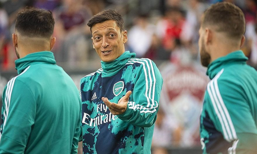 """Mesut Ozil of Arsenal joking with teammates while warming up before their game against the Colorado Rapids on Monday. Fans are increasingly frustrated with owner Stan Kroenke's """"passive"""" leadership."""