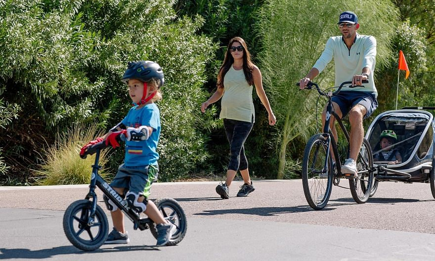Michael Phelps and his wife, Nicole, who is expecting their third child, take their two sons Boomer and Beckett around their neighbourhood in Paradise Valley, Arizona. In a week when he lost his remaining butterfly world records, the most decorated O