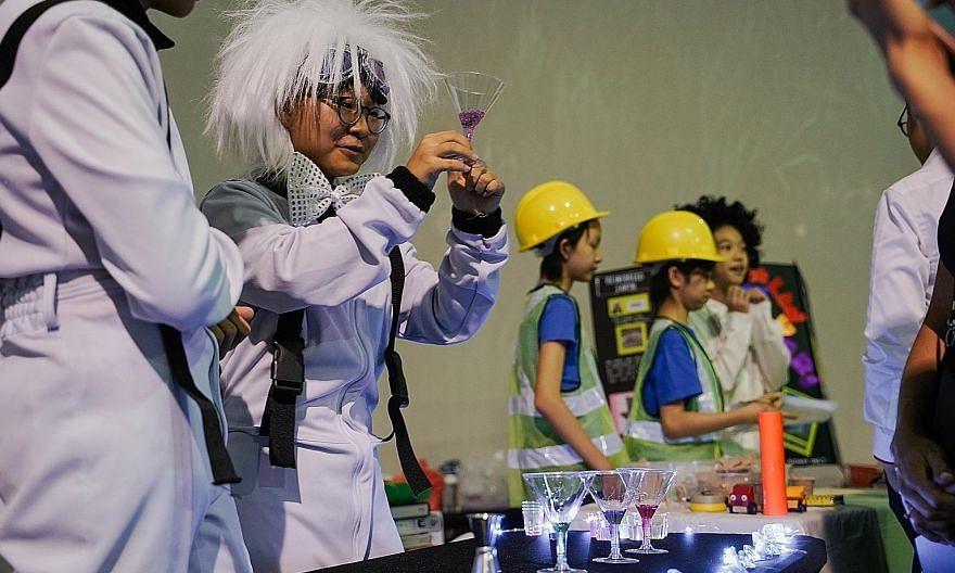 Participants demonstrating a science experiment during a media preview of the Singapore Science Festival on Tuesday. The festival will take place from tomorrow to Sept 15.