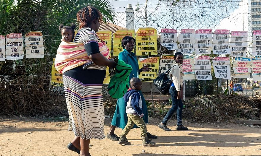 Signs of various newspapers on the streets of Harare on Friday about former Zimbabwe president Robert Mugabe, following his death. Visitors arriving yesterday at the Singapore Casket funeral parlour, where the body of Mr Mugabe rests. The date of the