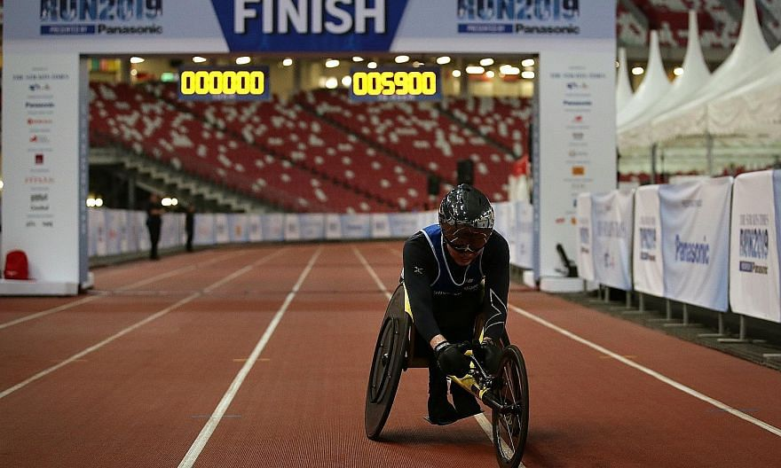 Paralympian wheelchair racer William Tan finishing the 18.45km race yesterday. He was the lone participant in his race and was making his official debut in the ST Run this year. He hopes his participation will encourage fellow wheelchair racers to take pa