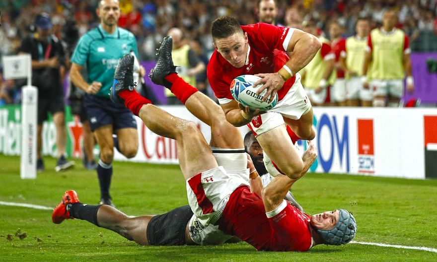 Josh Adams crossing the line to score his third try in Wales' 29-17 win over Fiji in Pool D at the Oita Stadium yesterday. The bonus-point win booked Wales their last-eight ticket. PHOTO: REUTERS