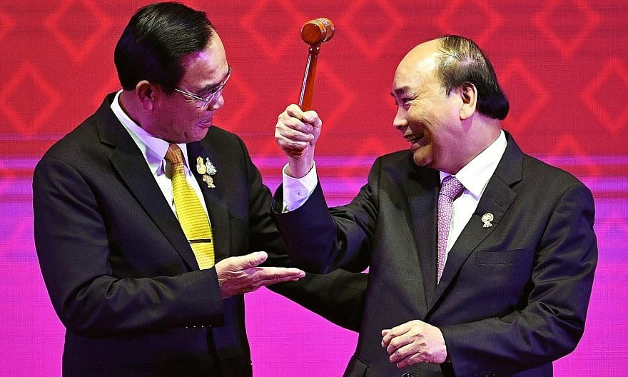 Vietnam's Prime Minister Nguyen Xuan Phuc (far right) holding the symbolic chairman's gavel after receiving it from Thailand's Prime Minister Prayut Chan-o-cha during the closing ceremony of the 35th Asean Summit and related summits. The 10 Asean mem