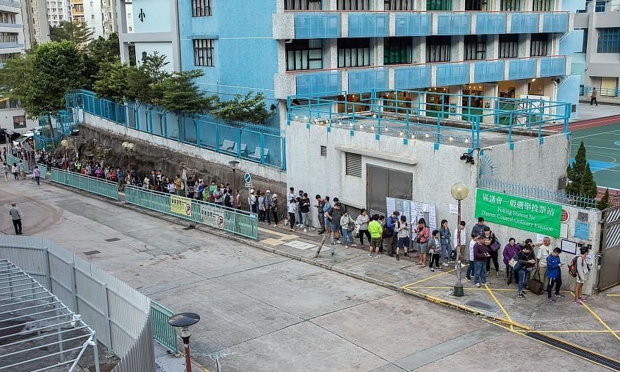 Voters queueing outside a polling station during the district council election in Lam Tin, Hong Kong, yesterday. PHOTO: BLOOMBERG
