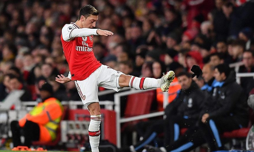 Arsenal's Mesut Ozil kicking his gloves in anger after his substitution during the 3-0 loss to Manchester City on Monday.