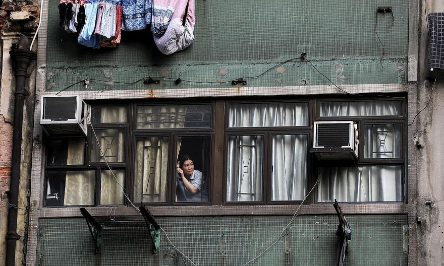A Hong Kong resident watching anti-government protests from her apartment window in October. The often violent demonstrations have been dragging on, upsetting the lives of the city's residents. Safety concerns, daily inconveniences and economic woes