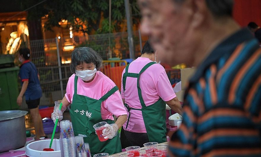 Food handlers at the Loyang Tua Pek Kong Temple wore masks as a safety precaution. The celebrations this year saw a smaller than usual turnout, with just 3,000 attending, compared to 5,000. Left: Staff from the Hindu Endowments Board monitoring therm
