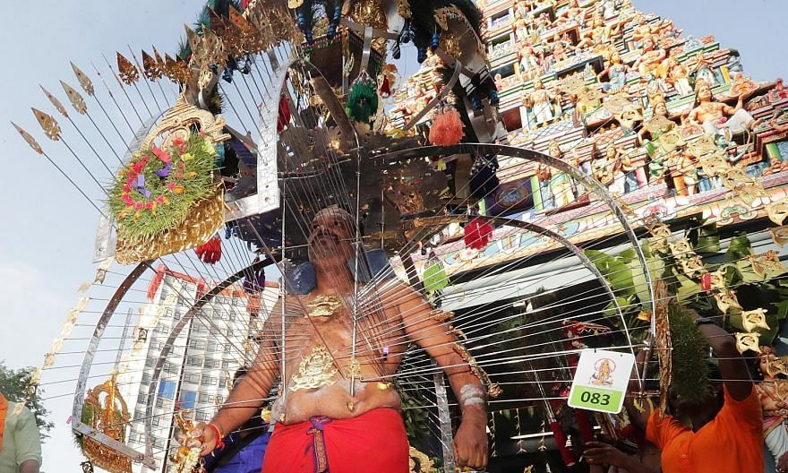Minister for Communications and Information S. Iswaran applying holy ash on a devotee's forehead as a symbol of protection against evil forces. Above: A kavadi-bearer at the start of the Thaipusam procession at Sri Srinivasa Perumal Temple in Serango