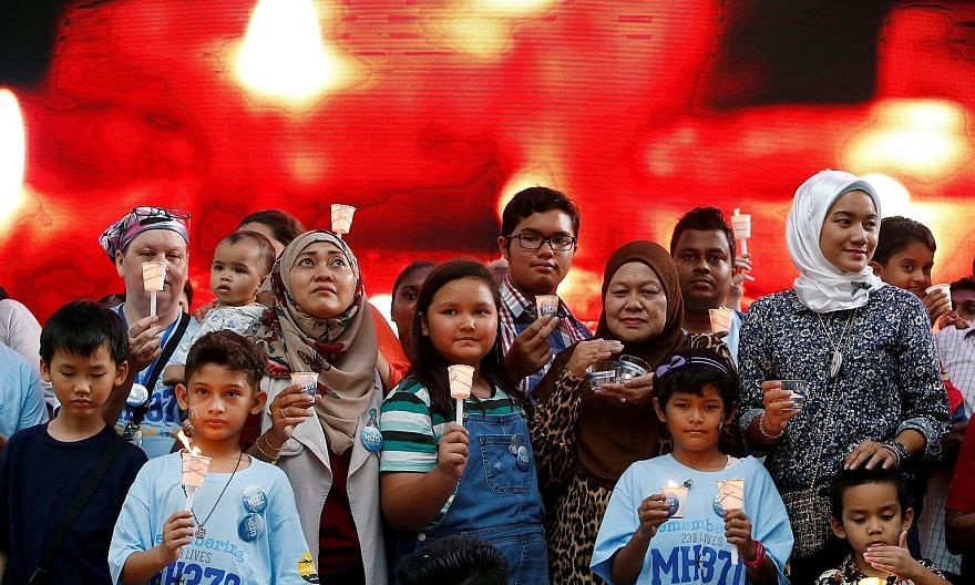 Family members holding candles during the fifth annual remembrance event for the missing Malaysia Airlines Flight MH370 in Kuala Lumpur in March last year. PHOTO: REUTERS