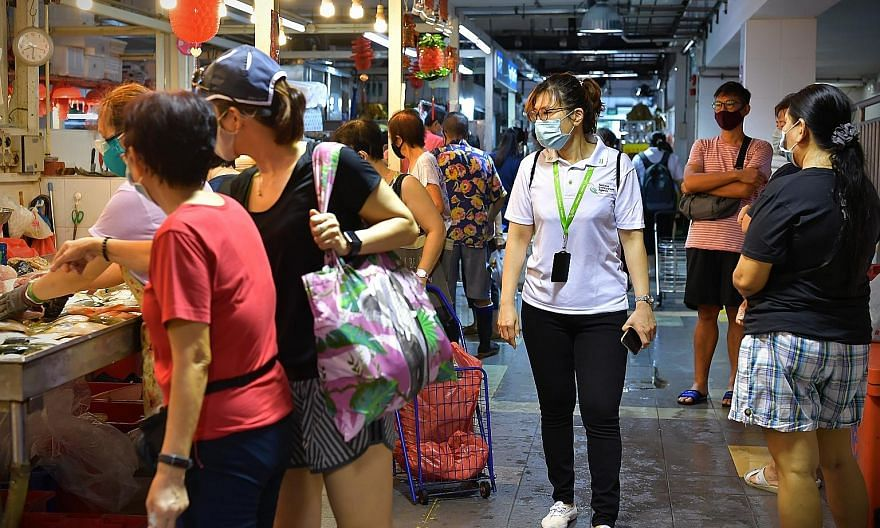 People waiting to enter FairPrice in Tampines Mall yesterday evening, as part of crowd-control measures. A National Environment Agency officer at Holland Drive Market and Food Centre yesterday morning, helping to ensure that the shoppers there were o