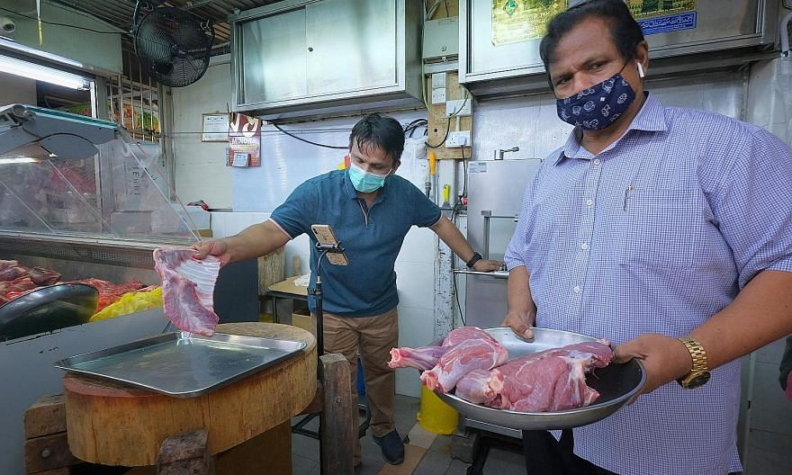 People at Tekka Market yesterday afternoon. Some stalls have reported sales plummeting by up to 80 per cent amid the pandemic. ST PHOTO: GAVIN FOO Mr Mohamed Mustafa Shahul Hamid (at right), who runs a mutton stall at Tekka Market, and his son Nizamd