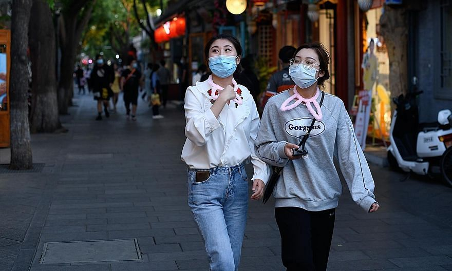 Women in masks visiting a Beijing shopping alley on Wednesday. Premier Li Keqiang said 70 per cent of the funds in the stimulus package he unveiled last week will go directly to supporting small and medium-sized enterprises, and spur consumption.
