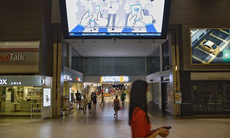 An advisory for the TraceTogether app being shown on a giant screen at Junction 8 mall on Sunday. ST PHOTO: DESMOND WEE