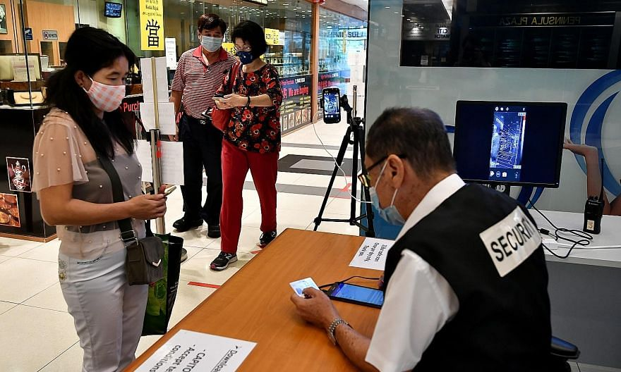Security staff at Peninsula Plaza checking visitors' identity cards yesterday as part of contact tracing measures during phase one of the post-circuit breaker period.