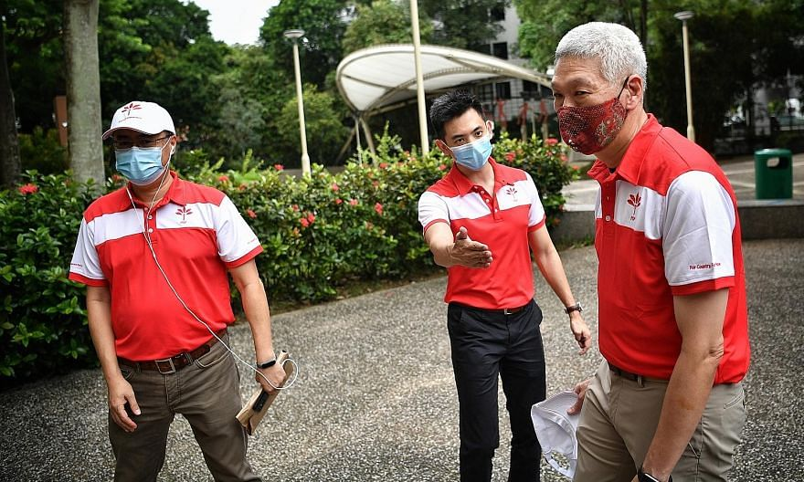 (From left) PSP members Michael Chua, Terence Soon and Lee Hsien Yang on their walkabout in Holland Close yesterday. Mr Lee, Prime Minister Lee Hsien Loong's brother, did not say if he would contest the election.