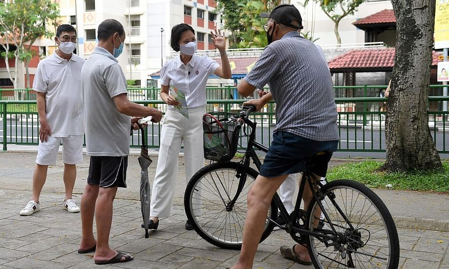Dr Ang Yong Guan, the PSP's candidate for Marymount, giving out face masks to residents during his walkabout in Sin Ming Road yesterday. The WP's Ms Tan Chen Chen, who is contesting in Punggol West, giving her speech at St Anthony's Canossian Primary