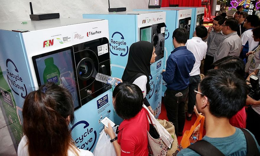 """The """"reverse"""" vending machines during their launch at Our Tampines Hub last October. The older machines (above) dispense a 20-cent FairPrice discount voucher for every 20 containers deposited. The new machines offer more reward choices, including fre"""
