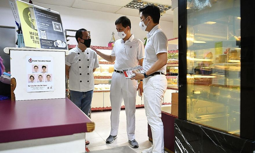 People's Action Party candidates for Tanjong Pagar GRC Chan Chun Sing (centre) and Alvin Tan speaking to Mr Teo Choon Khng, 60, at a bakery in Owen Road yesterday.