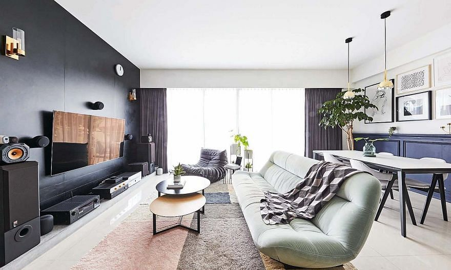The dark hues from the TV feature wall and audio devices in the living room are contrasted with the light colours found in soft furnishings such as rugs, a fabric sofa and a lounge chair.