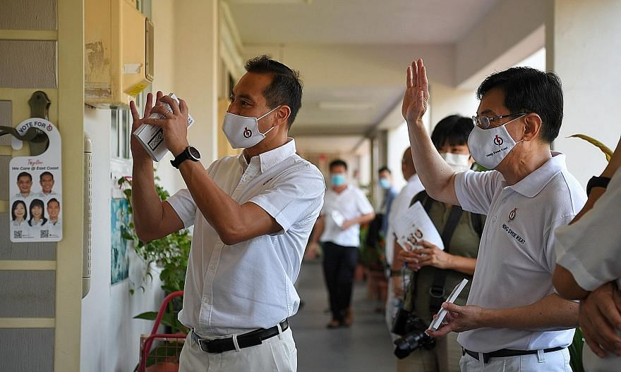 Deputy Prime Minister Heng Swee Keat and new face Tan Kiat How greeting residents during a block visit in Bedok North Street 1 yesterday.
