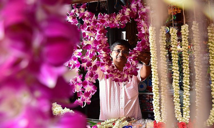 While vendors such as Mr Rajakumar Chandra (top), who sells flower garlands, may receive fewer orders from political parties this year, others like Ms Sarah Tang (above right) and Ms Alison Schooling of graphic design studio Sarah and Schooling are e