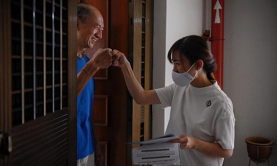 Ms Tin Pei Ling, the People's Action Party candidate for MacPherson SMC, giving a fist-bump to a resident during house visits at Block 122 Paya Lebar Way yesterday. She is defending the single seat against People's Power Party chief Goh Meng Seng.