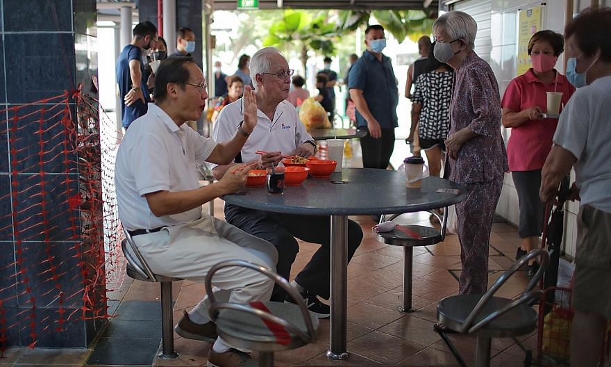 Emeritus Senior Minister Goh Chok Tong (second from left) and PAP candidate for Marine Parade GRC Tan See Leng greeting a resident while eating at Marine Terrace Market yesterday. Mr Goh recounted on Facebook how he had to confront critical issues si