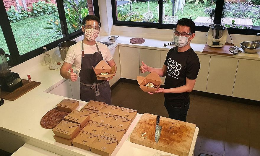 MasterChef Singapore winner Zander Ng (left) and GoodHood.SG founder Nigel Teo, with meals prepared by Mr Ng under the #KindCooks initiative, which connects neighbours who cook with those in need of meals. The initiative has seen 40 volunteers provid