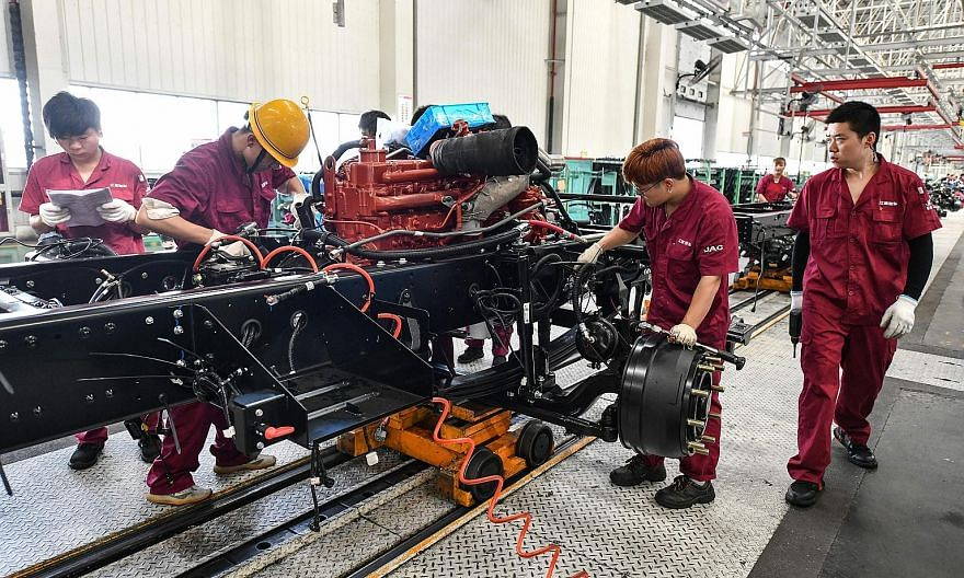 Employees working on a truck assembly line at a factory in Fuyang, in China's eastern Anhui province, yesterday. Official figures showed a 3.2 per cent growth in gross domestic product, a stunning recovery from a historic 6.8 per cent contraction las