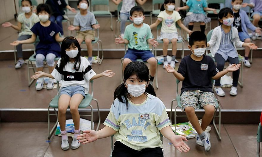 Pupils clapping along instead of singing a song during a music class at a school in Funabashi, east of Tokyo, yesterday. Tokyo reported a daily high of 286 new cases yesterday. The uptick has complicated a multibillion-dollar plan to boost domestic t