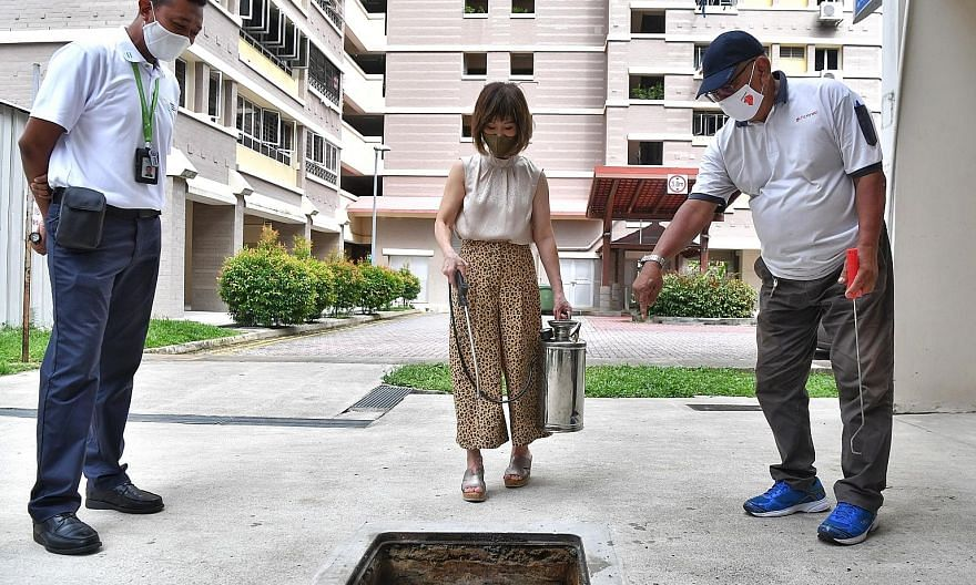 Senior Minister of State for the Environment and Water Resources Amy Khor trying her hand at oiling the drains at Block 408 Bukit Batok West Avenue 4 yesterday. ST PHOTO: CHONG JUN LIANG