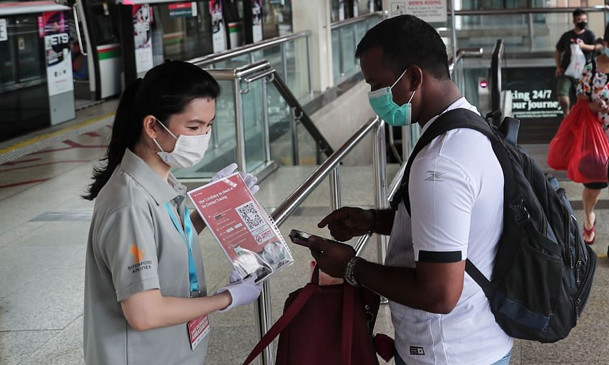 A transport ambassador reminding a commuter to check in, using the SafeEntry QR code, at Jurong East MRT station last month.