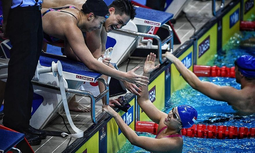 Joseph Schooling and Roanne Ho congratulating Amanda Lim after she anchored the mixed 4x50m medley relay quartet to second place at the 2018 Fina Swimming World Cup.