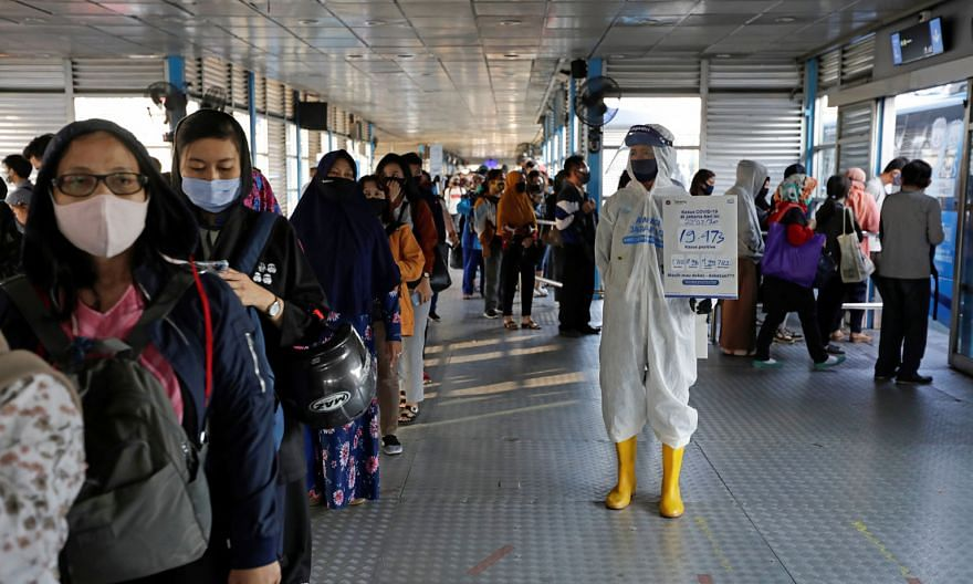 A worker at a central bus hub in Jakarta holding a placard with the total number of positive Covid-19 cases on Monday written on it. Since the middle of the month, some 45 clusters - of two or more simultaneous infections - have emerged as residents