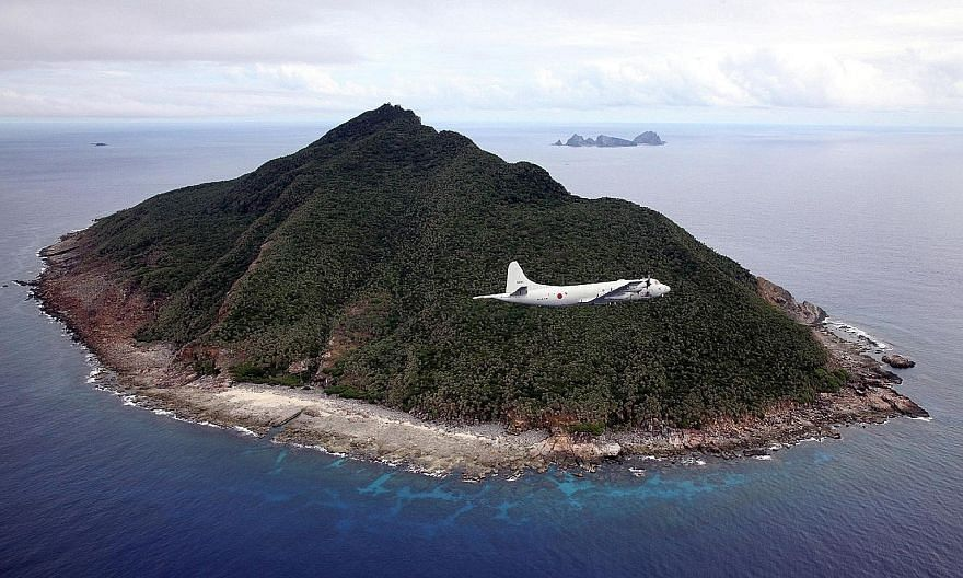 A 2011 file photo of a Japanese Maritime Self-Defence Force patrol plane flying over the East China Sea islets called the Senkaku Islands in Japan, and Diaoyu Islands in China. The writer says the dispute over the islets is one example of a deficit o