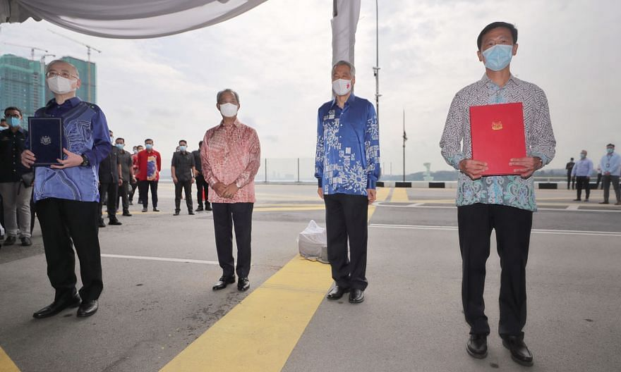 Singapore Transport Minister Ong Ye Kung (right) and Malaysian Transport Minister Wee Ka Siong (left) at yesterday's ceremony at the Causeway, where they presented the signed bilateral agreement on the RTS Link project to each other. The ceremony was