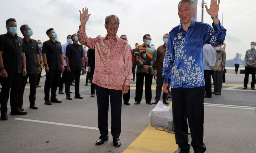 Prime Minister Lee Hsien Loong and Malaysian Premier Muhyiddin Yassin at a ceremony held at the Causeway yesterday to mark the resumption of the RTS Link project. The thick yellow line marks the international boundary. ST PHOTO: GAVIN FOO