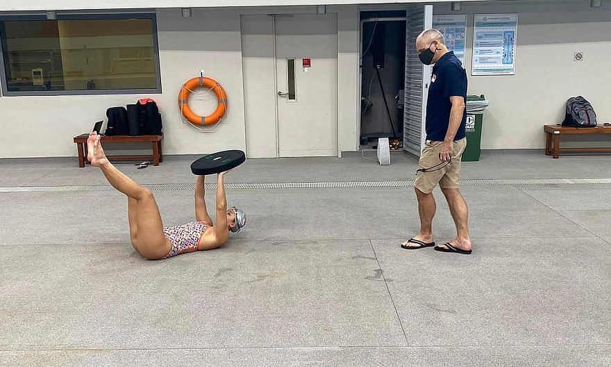 National swimming coach Stephan Widmer, his mask on, keeps the appropriate social distance as he monitors the progress of Amanda Lim at the OCBC Aquatic Centre.