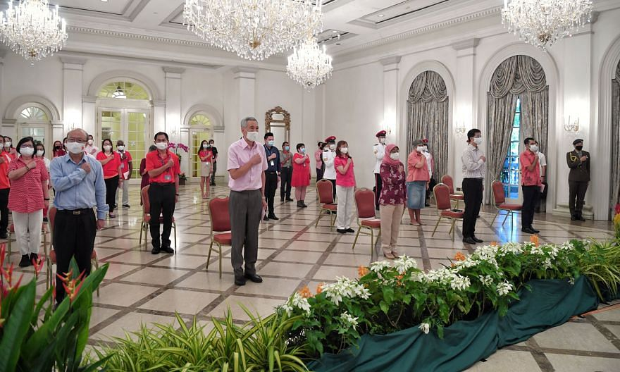 The National Day observance ceremony at the Istana yesterday was a smaller, quieter affair due to Covid-19. President Halimah Yacob and Prime Minister Lee Hsien Loong were joined by the Istana's and Prime Minister's Office staff, including (left) Cab
